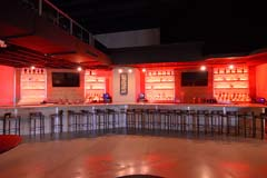 Banquet hall entertainment center with full bar with red ambient lighting by Paramount Construction and Contracting